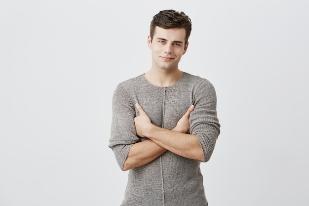 Горизонтальная картина привлекательного уверенного темноволосого молодого человека со стильной стрижкой, стоящего на сером фоне глухой стены с копией пространства, широко улыбающегося и держащего руки сложенными