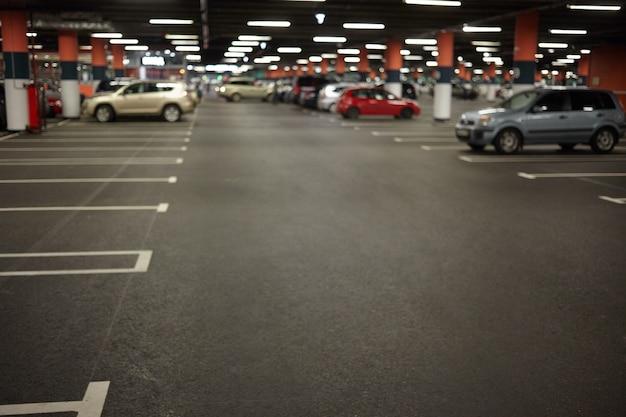 ネオンライトと自動車が駐車されている駐車場または地下駐車場の内部の水平方向の写真。建物、都市建設、宇宙、交通、車両、夜の街のコンセプト