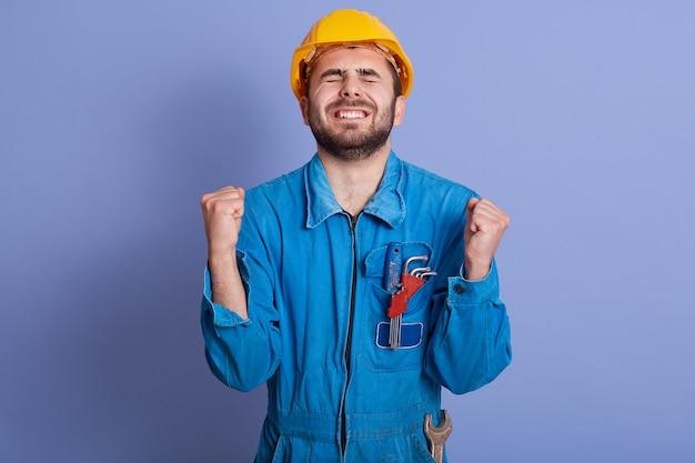 疲れきった建設労働者が拳を握り締め、手を上げ、目を閉じ、仕事に疲れて、青い制服を着て、窮屈な小屋を抱えている水平方向の画像。人と営業日のコンセプト。