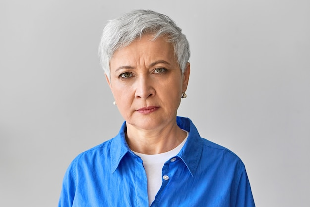 Horizontal picture of serious grumpy gray haired mature businesswoman in stylish blue shirt expressing negative emotions, frowning eyebrows, displeased with late employee or missed deadline
