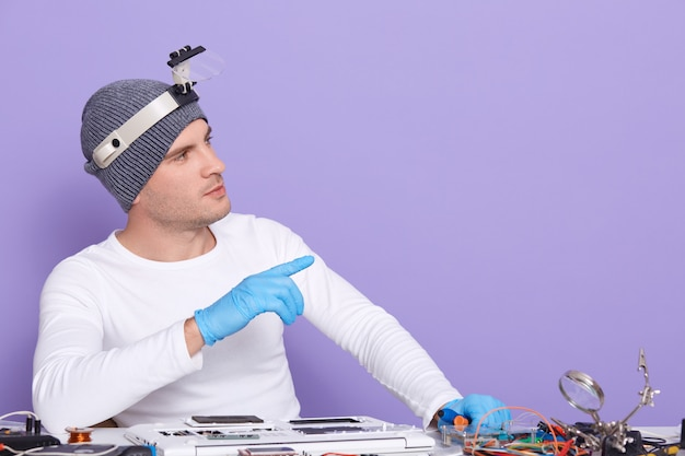 Horizontal picture of young professional electronic engineer fixing laptop, making gesture, looking aside, using equipment