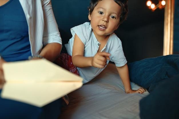 Ritratto orizzontale di adorabile ragazzino attivo che gioca in camera da letto, puntando il dito sul davanti