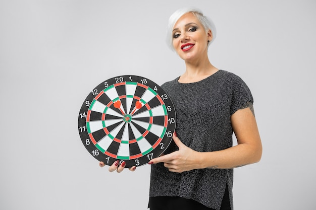 Horizontal portrait of adult blonde woman with board for darts