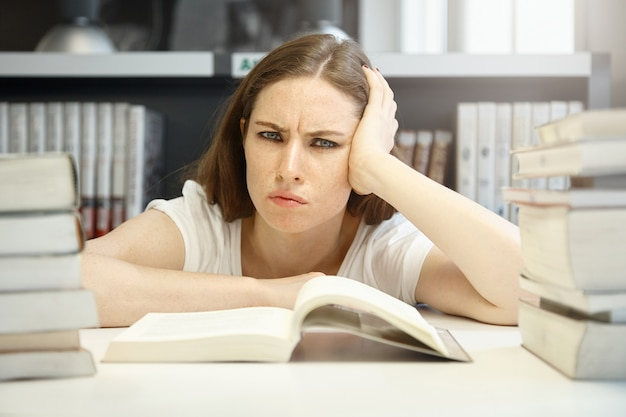 Ritratto orizzontale di donna adolescente arrabbiata, triste e frustrata che indossa abiti casual e trucco quotidiano, annoiata dallo studio di un manuale scientifico presso la biblioteca della scuola, con sguardo scontento e cattivo umore
