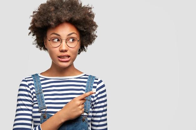 Ritratto orizzontale della femmina afroamericana attraente con l'espressione perplessa