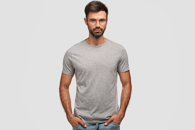 Horizontal portrait of attractive bearded male with serious expression, dressed in casual grey t-shirt, keeps hands in pockets, shows new clothes, isolated over white wall. people, style concept
