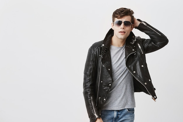Horizontal portrait of attractive caucasian man with sunglasses on, stylish haircut, dressed in black leather jacket, looks seriously into camera. muscular handsome male model poses in studio