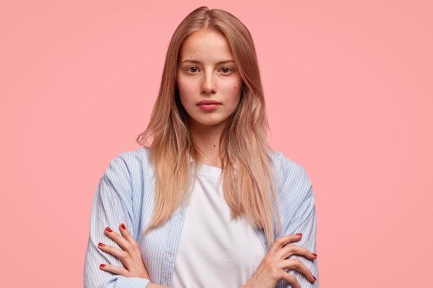 Horizontal portrait of attractive serious european female keeps hands crossed and looks self assured