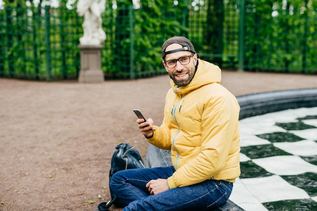 Horizontal portrait of bearded hipster male looking aside with delightful expression while sitting