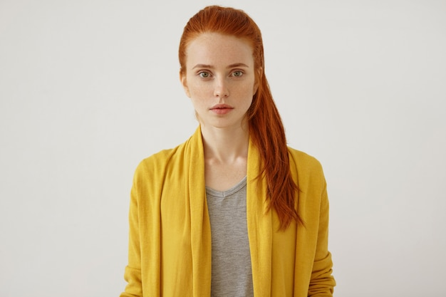 Horizontal portrait of beautiful young female lady with freckles ang ginger pony tail, wearing yellow clothes, having full lips and green shining eyes, looking directly with confidence