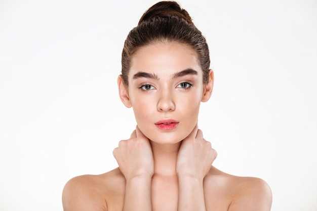 Horizontal portrait of beautiful young woman with fresh skin touching her neck posing with meaningful look