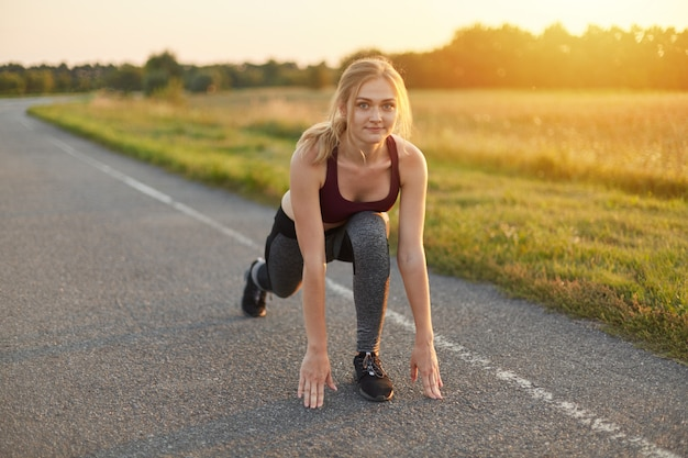 Horizontal portrait of blonde female, wearing top, trousers and sport shoes, doing exercises on road, stretching her legs, being full of energy. sporty woman warming up her legs before running