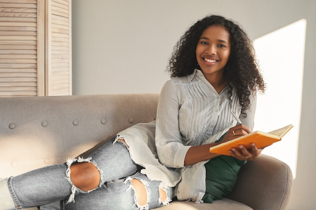 Horizontal portrait of charming positive young mixed race female in stylish shirt and ripped blue jeans smiling broadly, lying on couch with diary, planning vacations, feeling happy and inspired