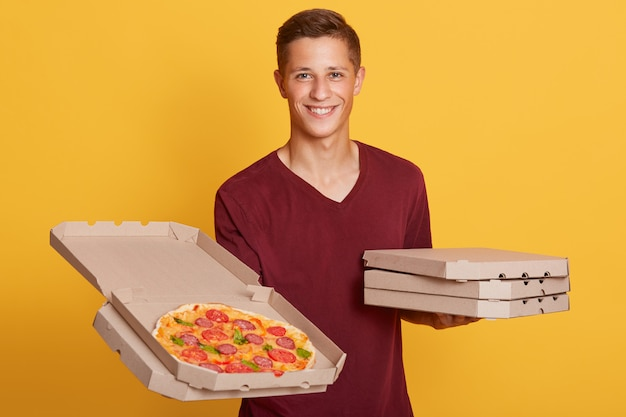 Horizontal portrait of cheerful charismatic courier looking directly, holding an open box of pizza