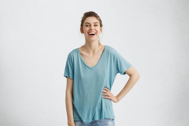 Ritratto orizzontale di giovane donna dagli occhi azzurri dai capelli biondi allegra che indossa jeans e t-shirt casual blu tenendo la mano sul polso avendo un aspetto rilassato mentre posa nel muro bianco