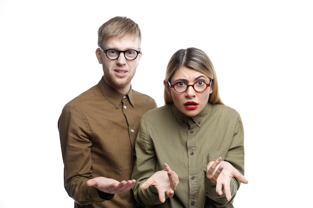 Horizontal portrait of clueless young caucasian man and woman making confused gestures while posing together, being lost for words, looking in indignation and irritation