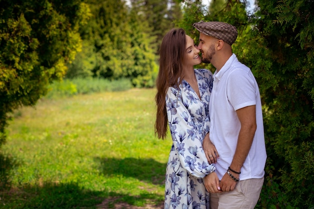Horizontal portrait of couple in love hugs and smiles holding hands at the green garden