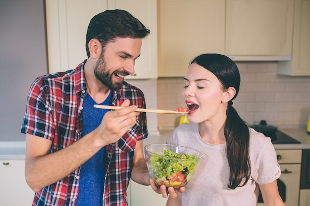Horizontal portrait of couple standing at kitchen. guy holds wooden spoon and feed girl.