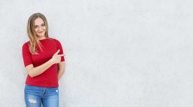 Horizontal portrait of cute woman wearing red sweater and jeans standing near white concrete wall poiting with her index finger