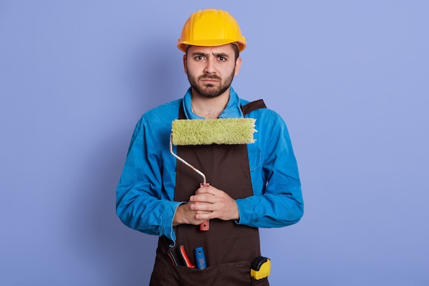 Horizontal portrait of displeased upset sad builder having frowned facial expression, having problems, holding roller in both hands. people and crisis concept.