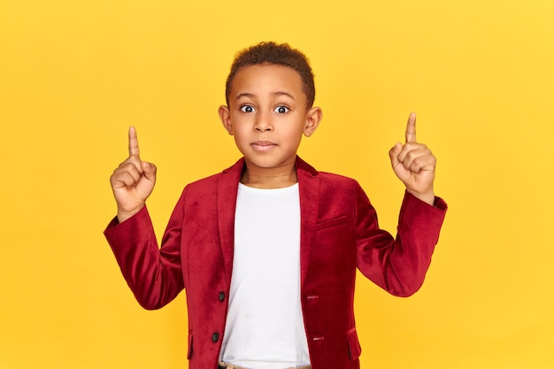 Ritratto orizzontale del ragazzo africano di otto anni emozionante emotivo che indica al contenuto interessante