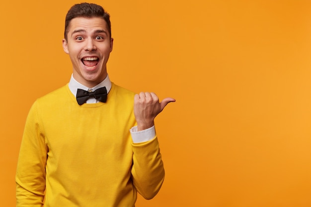 Horizontal portrait of excited attractive guy dressed yellow sweater and bow-tie, points with thumb