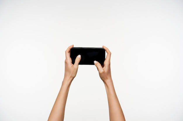 Horizontal portrait of fair-skinned pretty woman's hands holding smartphone and moving fingers on screen while being isolated on white
