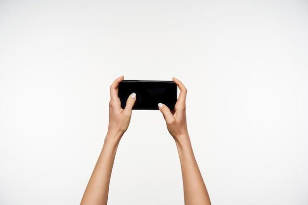 Ritratto orizzontale delle mani della donna graziosa dalla carnagione chiara che tengono smartphone e dita in movimento sullo schermo mentre è isolato su bianco