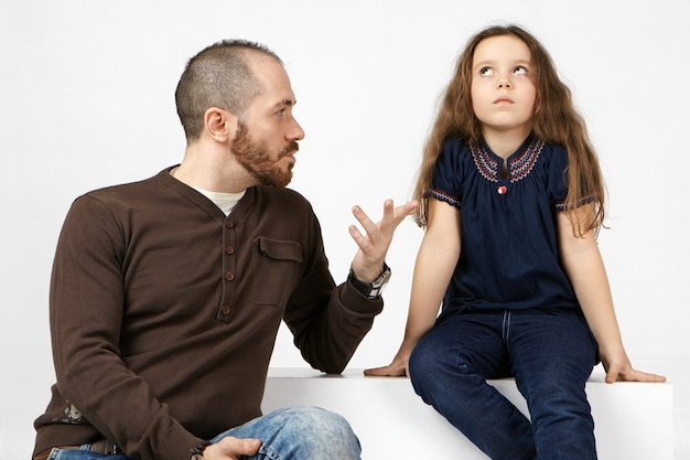 Horizontal portrait of fashionable young bearded male having serious conversation with his naughty spoiled female child, talking about rules to her.