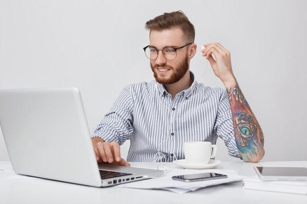Horizontal portrait of glad male office worker with thick beard, has coffee break