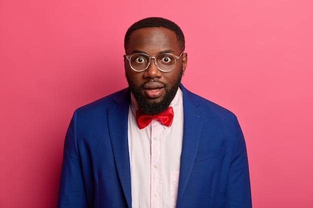 Il ritratto orizzontale del bell'uomo afroamericano guarda con meraviglia, ha il fiato sospeso, indossa un abito formale e occhiali da vista