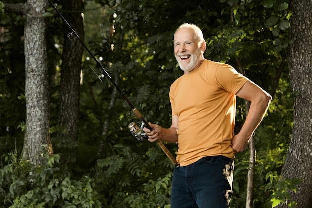 Horizontal portrait of handsome cheerful elderly caucasian male pensioner in casual clothes laughing happily while standing outdoors with fishing rod, catching fish on river bank in the morning