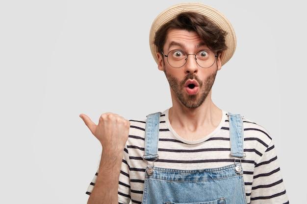 Il ritratto orizzontale del lavoratore agricolo maschio bello stupefatto tiene la bocca aperta, indica con il pollice sulla sinistra, mostra uno spazio vuoto, nota qualcosa di fantastico, isolato sopra il muro bianco