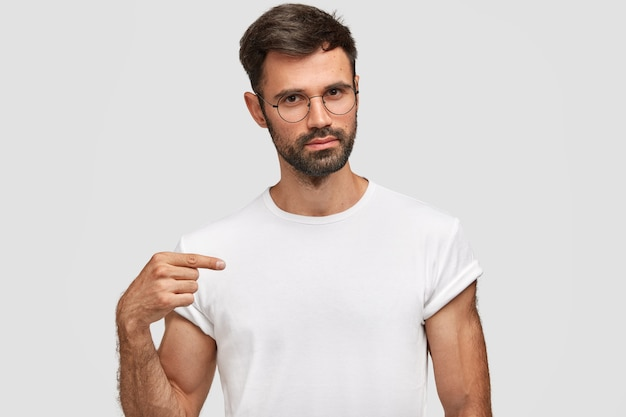Horizontal portrait of handsome unshaven male with stubble, dressed in casual white t-shirt, points at blank copy space for your design, wears spectacles. serious man seller of clothes