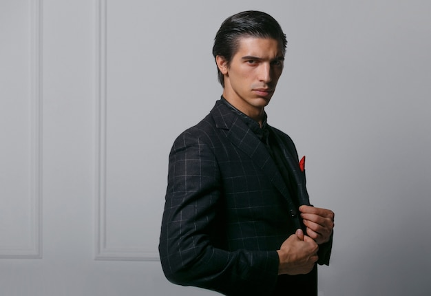 Horizontal portrait of handsome young man in black suit with red silk scarf in pocket, poses in profile, over white background.