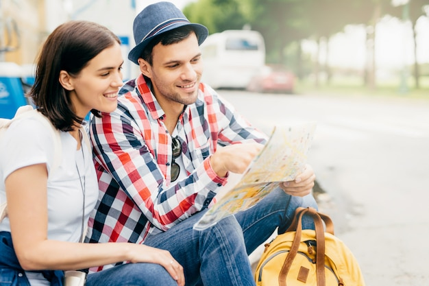 Horizontal portrait of happy couple, resting together outdoors, sitting on bench, looking in city guide, having gentle smiles, searching for place where to go. people, vacation, tourism concept
