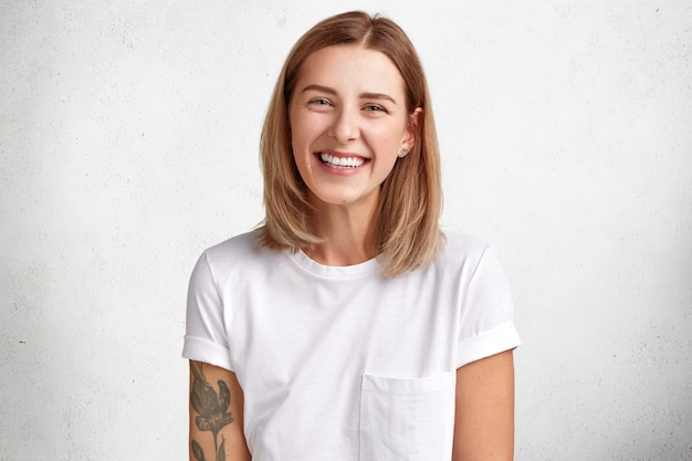Horizontal portrait of happy female has cheerful expression, dressed in white casual t shirt, expresses positiveness, being glad to spend free time with boyfriend.