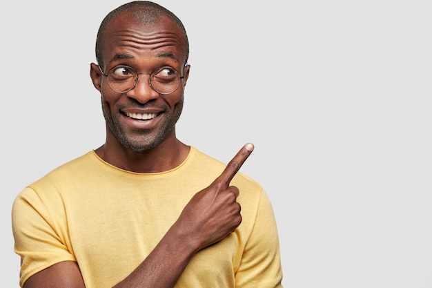 Horizontal portrait of happy man looks joyfully aside, points with fore finger at upper right corner