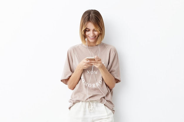 Horizontal portrait of happy smiling female with bobbed hairstyle dressed casually being happy to recieve invitation for birthday party from friend, typing answer, promising necessarily to come
