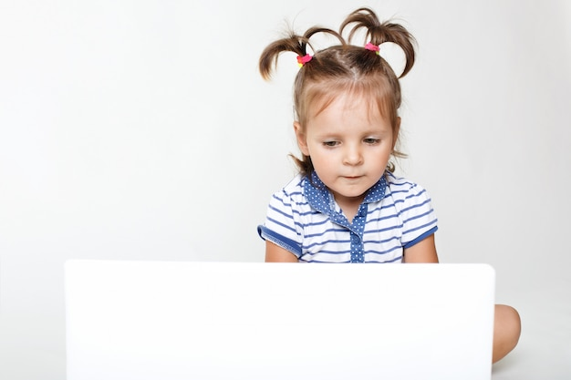 Horizontal portrait of little pretty girl focused into laptop computer, watches interesting cartoon or play games, has two pony tails, isolated over white studio wall. children and entertainment