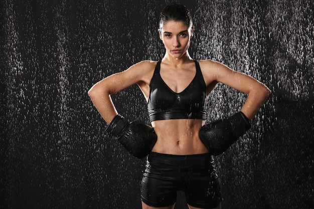 Horizontal portrait of muscular concentrated woman putting arms in boxing gloves on waist and looking on camera under rain drops, isolated over black background