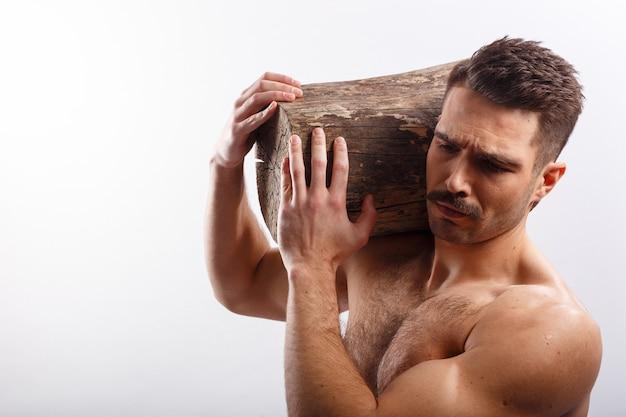 アスリート、セクシー、absの残忍なひげを生やした男の散髪、裸の胴体、白い背景の上の彼の肩に木の幹を持っての水平方向の肖像画。