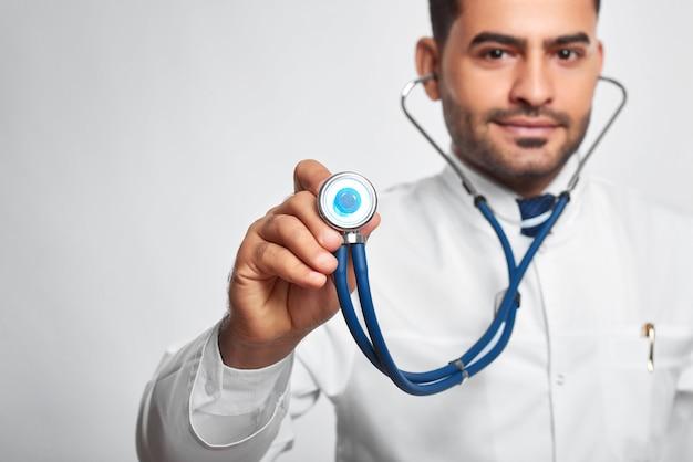 Горизонтальный портрет красивого бородатого мужчины-доктора, позирующего со стетоскопом на фоне серой стены, обследование медицины осмотра здравоохранения, обследование диагностики, клиническое обследование.