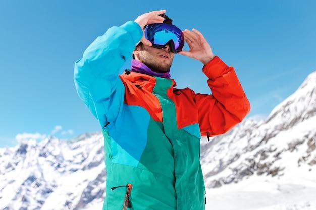 Горизонтальный портрет молодого лыжника, в лыжных очках в горах и смотрящего на солнечное небо