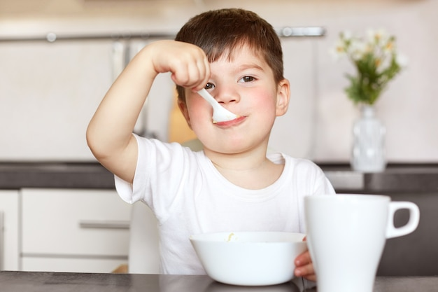 魅力的な男性の子供の水平方向の肖像画は牛乳とおいしいお粥を食べる