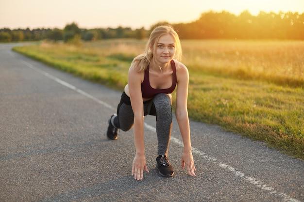 トップ、ズボン、スポーツシューズを履いて、道路で演習を行ったり、足を伸ばしたり、エネルギーに満ちている金髪の女性の水平方向の肖像画。実行する前に彼女の足をウォーミングアップスポーティな女性