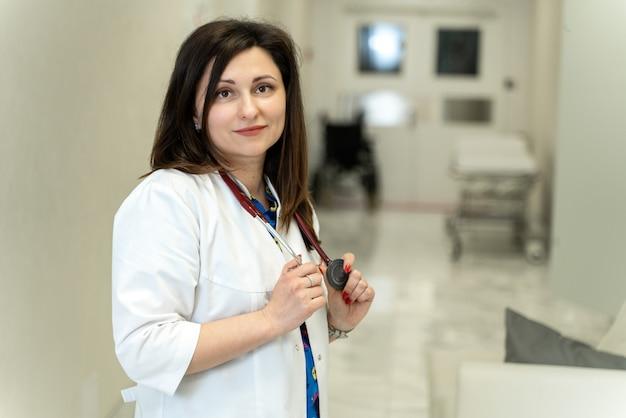 現代の病院に立って、良い気分でカメラに微笑んでいる陽気なブルネット白人女性専門看護師またはヘルスケアアシスタントの水平方向の肖像画。医師のコンセプト