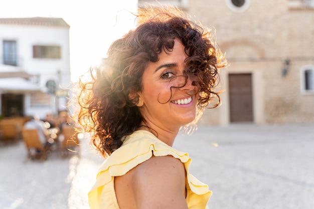 アンダルシアを観光するスペインの巻き毛の女性の横向きの肖像画。旅行と休日のコンセプト。