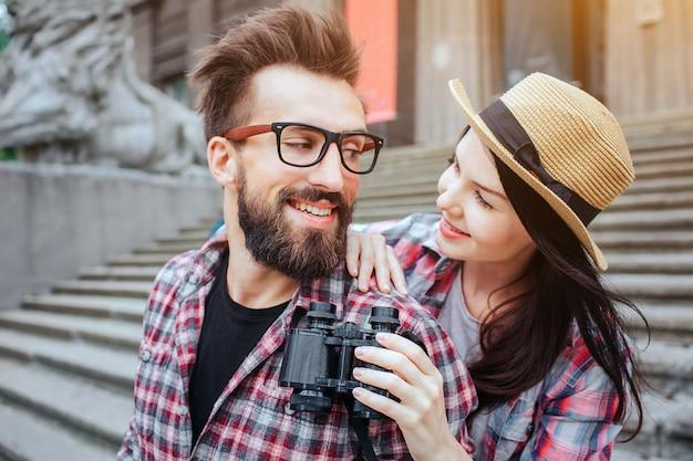 행복한 커플 서서 서로를 찾고 가로 세로. 그녀는 그 뒤에 있습니다. 긍정적 인 수염 여행자는 거꾸로 보인다. 그녀는 쌍안경을 가지고 있습니다.