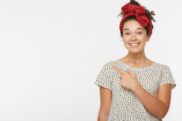Горизонтальный портрет модели счастливой женщины указывает указательным пальцем сбоку